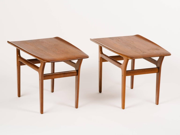 Pair of teak Mid-Century Modern end tables with streamline design. Fabulous sleek angles throughout, with tapered leg design and slightly curved tops. Stamped Denmark on the underside of tables.