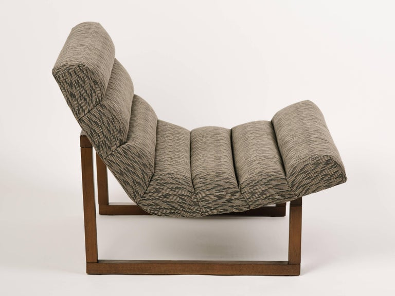 Mid-Century Modern lounge chairs with floating scoop seats and streamline walnut wood frames. Great looking from all angles, and featuring horizontal channel tufting. Upholstered in woven cotton blend fabric with geometric print in hues of taupe,