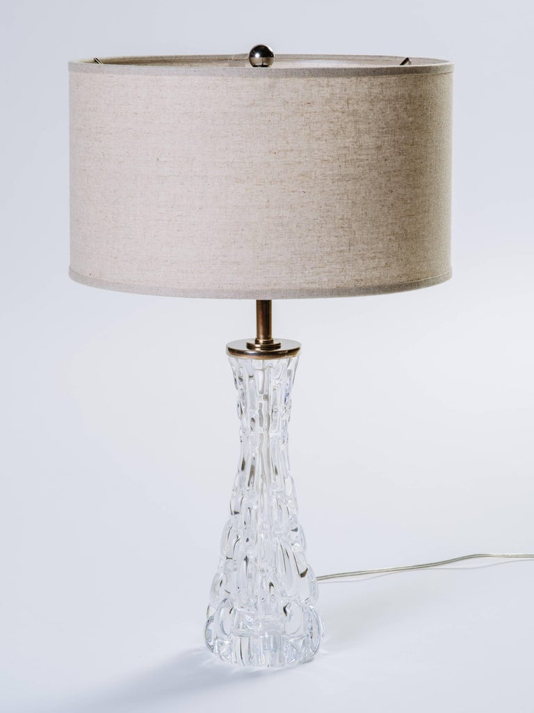 Pair of stunning Mid-Century Modern Swedish crystal lamps. The lamps have hourglass forms with textured ice glass design. Nickeled stem and fittings and shown with custom pale grey linen drum shades.