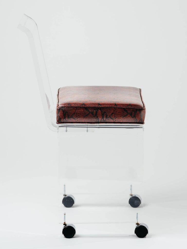 Mid-Century Modern Lucite vanity chair in genuine leather with embossed snakeskin in deep red. Stool has sleek lines with full back design, and polished beveled edges. Features swivel casters for effortless movement.