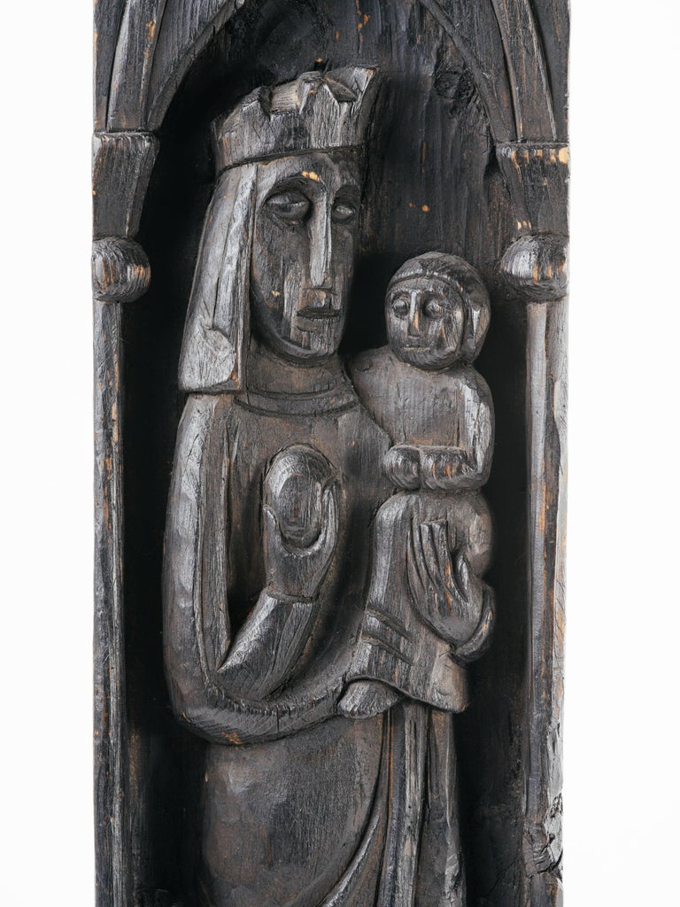 Victorian solid wood plaque with hand-carved designs, depicting religious or royalty figures. The carving features Gothic arches and columns with floral shields along the bottom. Has ebony finish and fitted with small hook for wall mounting.