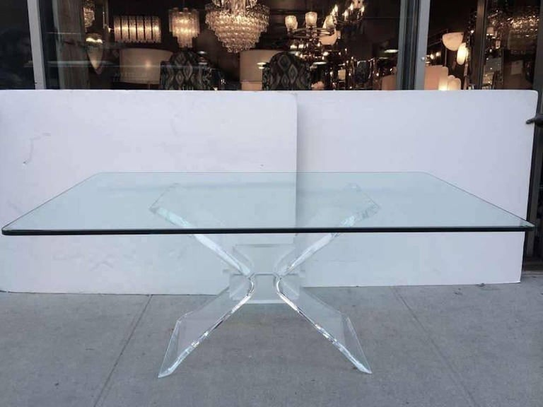 Mid-Century Modern dining table with hand beveled glass top and architectural butterfly base design. Base is comprised of thick sculptural Lucite with frosted Lucite block centre and rivets.