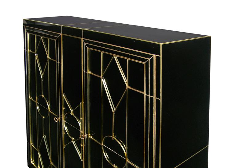 This late 1970s one-of-a kind Italian cabinet, from the North of Italy, entirely handmade, is covered in black glass highlighted with brass inlays. It is skillfully hand decorated with a bronze raised pattern on the front. The two doors are enclosed