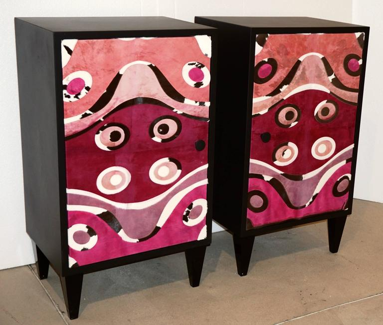 Contemporary fine design Italian pair of satin black lacquered side cabinets or nightstands raised on tapering wood legs, entirely hand made in Italy exclusive to Cosulich Interiors, the front crafted and decorated with a printed modern ethnic