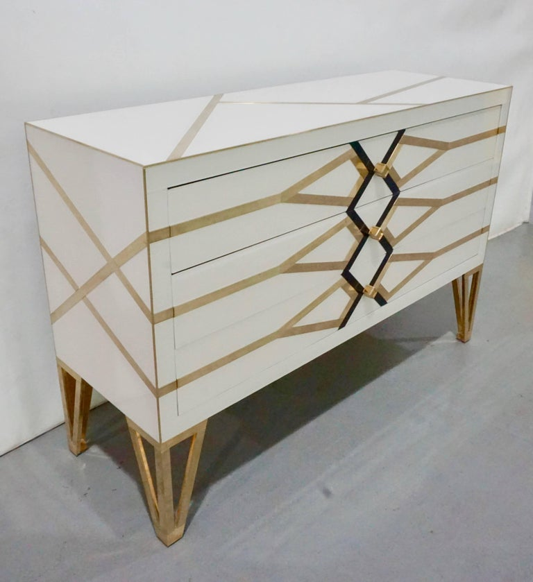 Italian three-drawer customizable commode, entirely handmade, exclusive modern Art Deco design by Cosulich Interiors, showing high quality and elegance of execution: the surround in ivory white is decorated with a geometric architectural abstract
