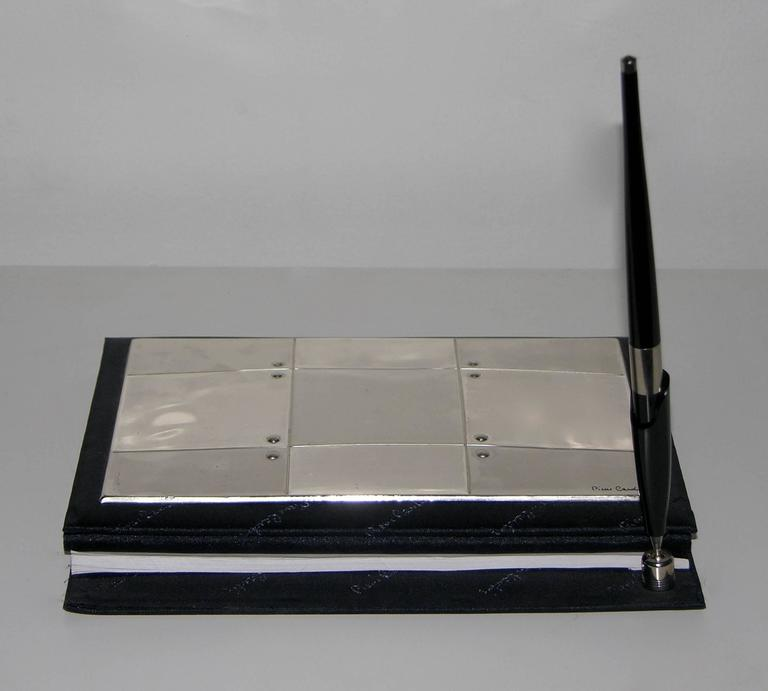 1980s desk set by Pierre Cardin, with original address book and notebook unused and in mint condition. The black fabric folder with embroidered Pierre Cardin signatures has a front cover in sterling silver with engraved signature and geometrically