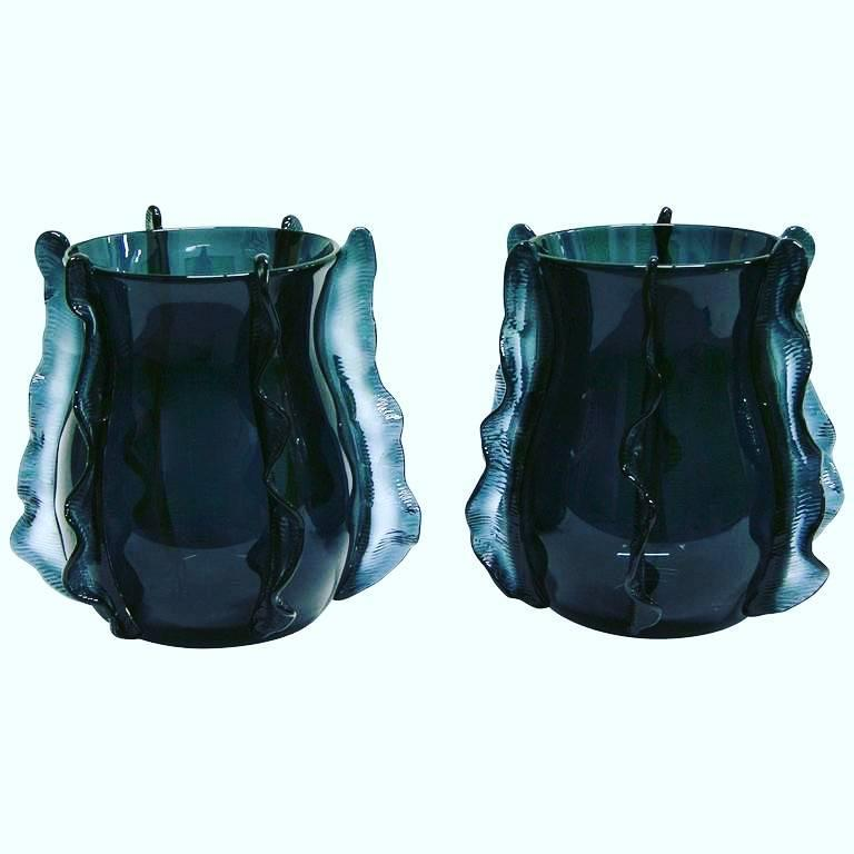 A Venetian pair of organic vases in blown Murano glass, created in a very rare avio blue color, the bombe´ shape sensually enhanced with waved handcrafted incised decorations in relief, like frills in motion that embrace and lift the design. Signed