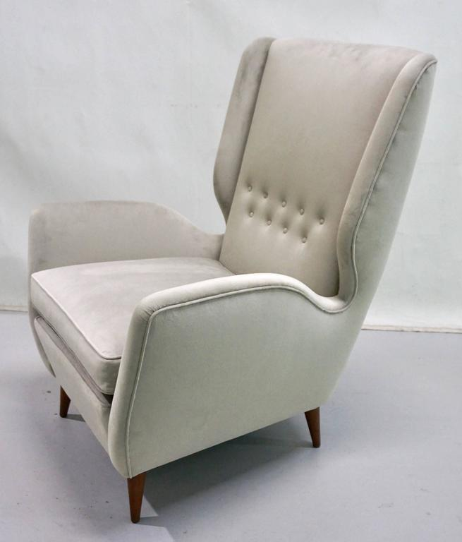These very comfortable high back armchairs by Gio Ponti, a statement of elegance and modern Italian Design, have very clean cut aerodynamic lines with very chic indented sides and slightly folded button-tufted back, raised on walnut legs. They are