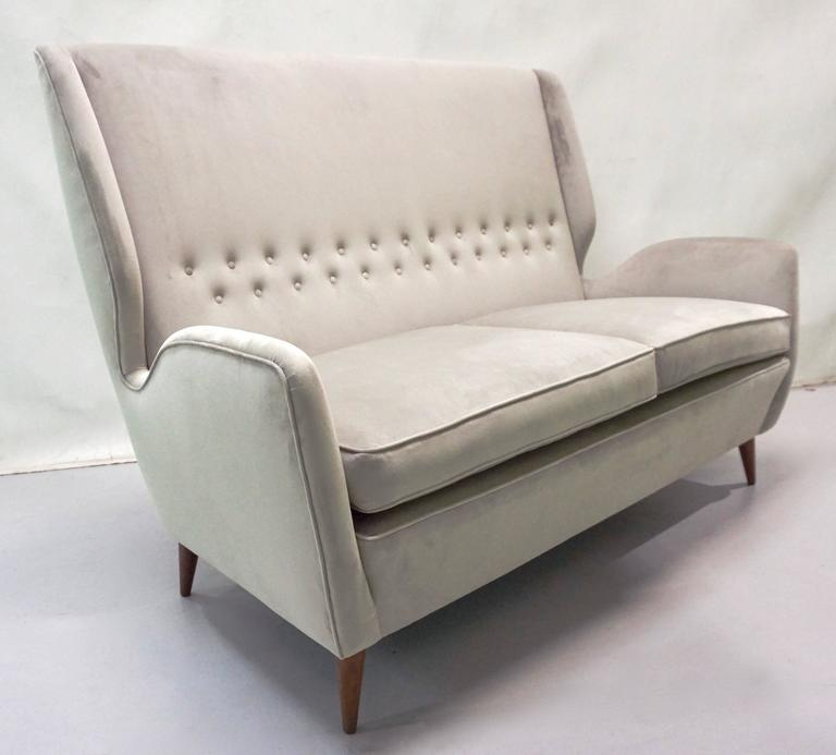 This comfortable settee by Gio Ponti, a statement of elegance and modern Italian design, has very clean cut aerodynamic lines with very chic indented sides and slightly folded button-tufted back, raised on walnut legs. It is upholstered in light