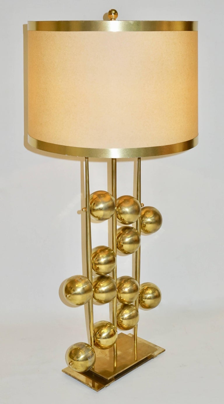 An exclusive organic pair of Italian lamps with a very unique and interesting abacus inspired design, entirely handcrafted, decorated with brass spheres in a zigzag pattern between handmade vertical brass poles, raised on a double stepped brass