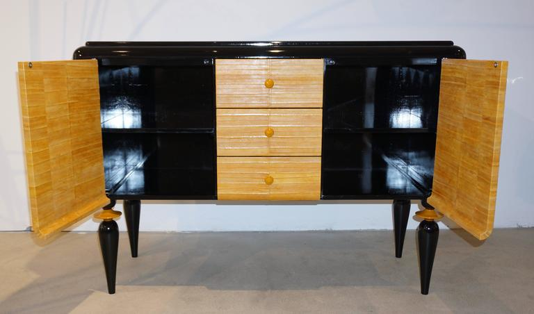 A contemporary fine design made in Italy case piece, credenza or cabinet of very high quality execution, entirely black lacquered, with stepped top surface, the front covered in yellow mustard genuine eel skin leather. The three central drawers with