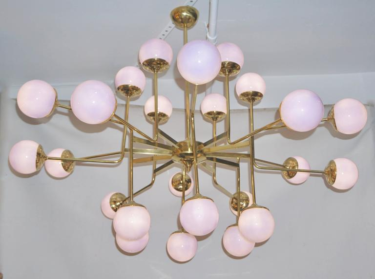 Contemporary made in Italy chandelier of exclusive fine design with a Sputnik inspiration, entirely handcrafted with a brass structure decorated with 24 blown Murano glass globes of rare and unusual lilac purple color, overlaid in white glass to