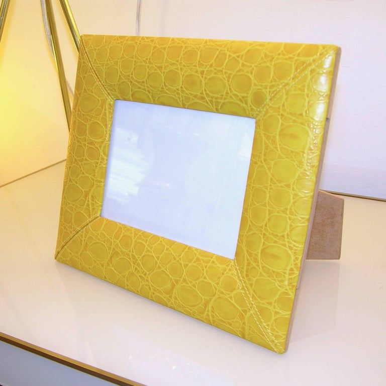 Modern photo frame of clean design, signed by the fashion designer Cesare Paciotti, high quality of Italian handmade execution, in stitched embossed leather in lemon yellow color, with beige felt back.