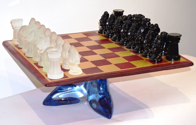 A very rare vintage Italian chess game of modern design by Ermanno Nason for Cesare Toso, the detailed chess pieces are molded in white frosted and black Murano Art glass, the blown glass board is in translucent red hand decorated with squares in
