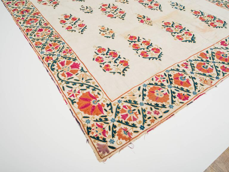 19th century Uzbekistani hand spun linen Suzani with silk embroidered floral motif and silk ikat border. Reverse side has original antique Fine hand printed cotton backing.