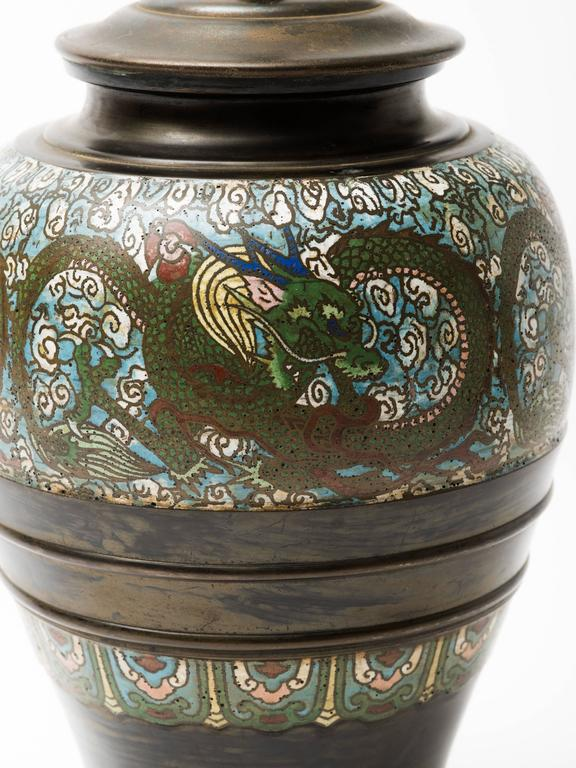 Bronze champlevé lamp with stylized dragon enameled cloisonné design surrounding and gorgeous patina. Mounted on hand-carved lacquered wood base, China, circa 1910-1920.