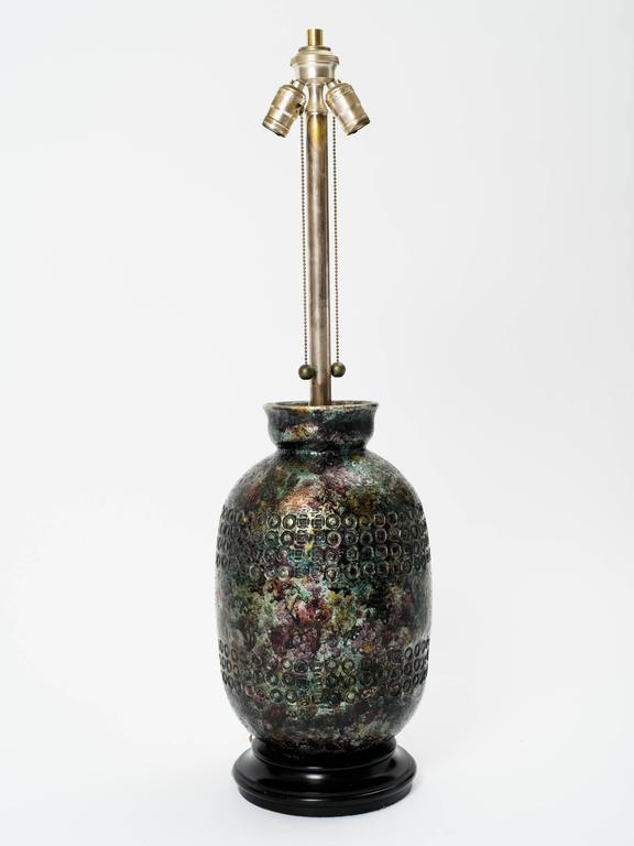 Monumental Aldo Londi for Bitossi metallic jewel glaze ceramic lamp. Circular ebonized wood base. Original double socket hardware with pull chains. Lamp body measures 15 inches height. Labeled, Marbro Lamp Company.