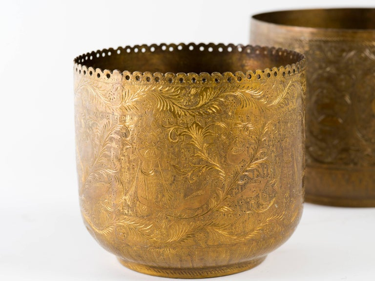 Pair of antique Indian hand-wrought brass vessels. They are completely and finely engraved with Indian gods, flora, and fauna. Large vessel measures 9 inches diameter x 7.5 inches diameter, small vessel 7.75 diameter x 6.75 height.