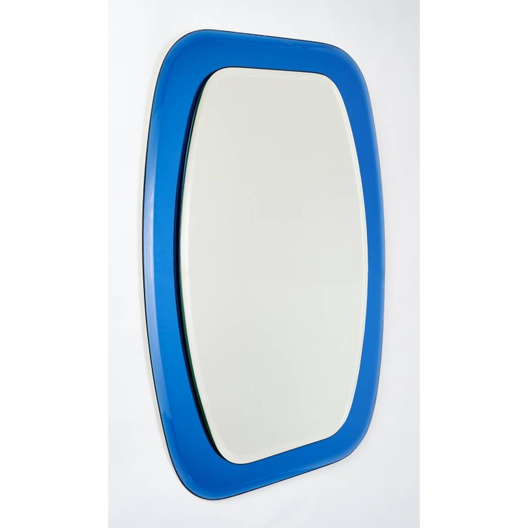 Italy, 1970s Shaped beveled mirror Mounted on a shaped beveled blue mirrored glass frame Measures: 23 W x 32 H.