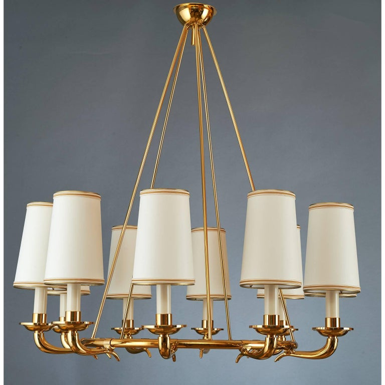 Italy, 1950s An elegant ten branch chandelier in polished brass  with gracefully styled cornucopia arms mounted on a suspended circular frame. 34 diameter x 35 H Rewired for use in the USA.