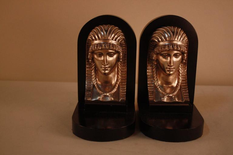 Pair of bookends with an Egyptian revival style, from the Art Deco period. Made of nickel on bronze, with lacquered marble for a sleek finish.