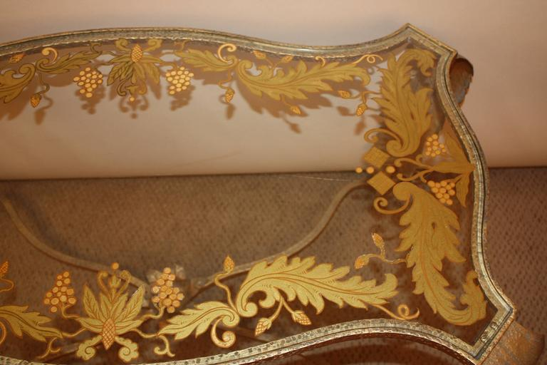 Wrought iron coffee table was finished in gold leaf with reverse paint glass top.