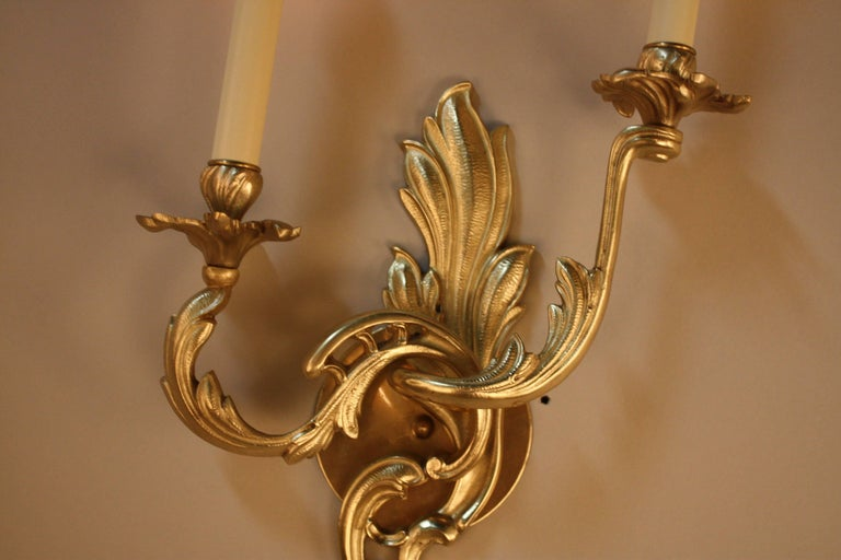 An elegant pair of double arm wall sconces. Made in France during the 1930s, this pair of sconces features beautiful bronze in an organically-inspired design; a classic example of Art Nouveau.