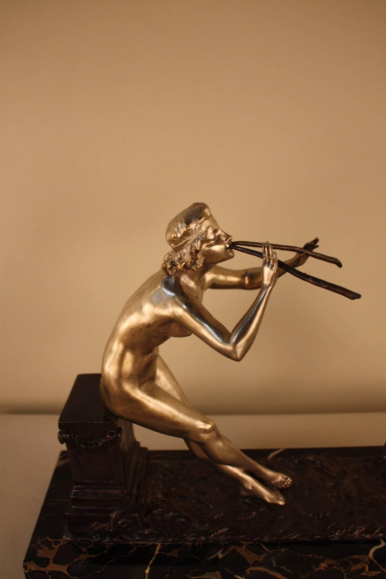 Bronze sculpture featuring a nude woman playing two horns while a small goat dances on two feet. 