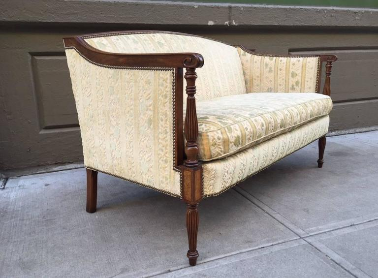 Two Regency style sofas with walnut frame. Carved fluted legs, original fabric and a loose cushioned seat.