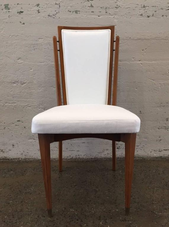 Set of six dining chairs. Frames of chairs are walnut and are newly upholstered in linen blend. Chairs have brass connectors and brass feet.  With arms:  37H x 22W  22D Without arms:  37H x 17.5W x 22D