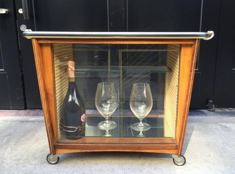 Bar has sliding glass doors, a black glass top with mother-of-pearl and brass inlay. Inside of bar has a brass bottle holder with caned sides and a mirrored bottom. Original casters and brass handles.  Bottle and glasses not included.