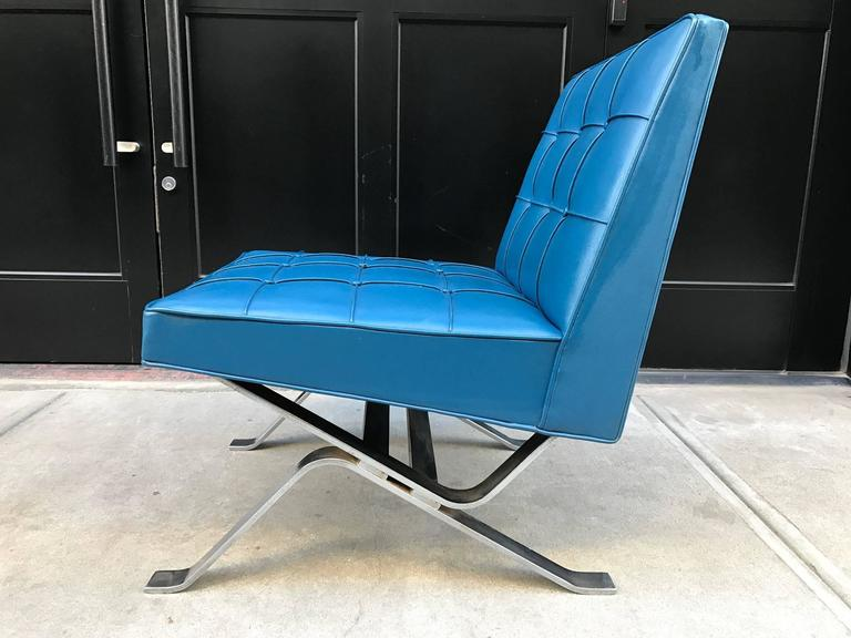 Pair of Robert Haussmann lounge chairs with chromed steel base and original blue vinyl upholstery. Milo Baughman style.