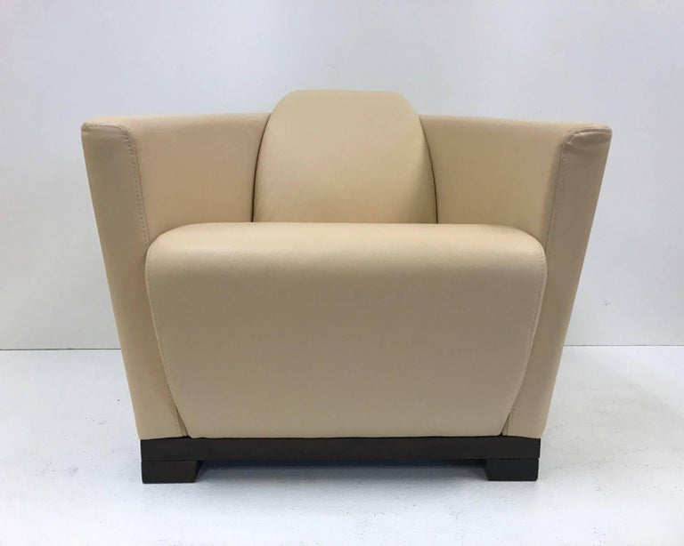 Pair of modern Italian leather club chairs by Calia. Has a dark walnut stained, solid wood base. Art Deco style.