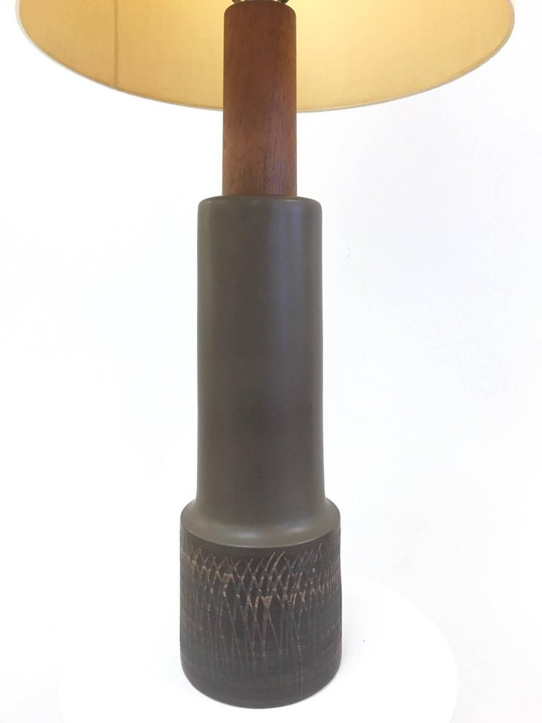 Tall Gordon Martz ceramic and walnut table lamp. Measures: 45.5 H (to top of finial) 7.25 in diameter (at widest). Shade not included.