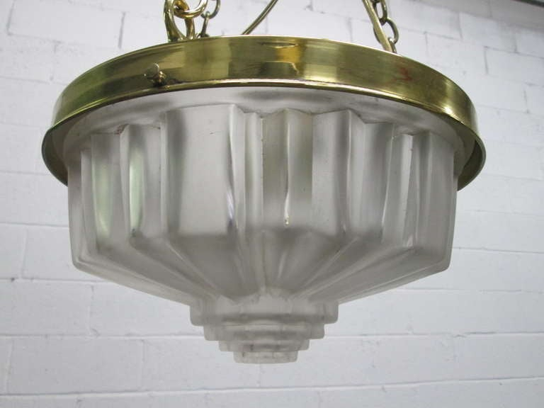 Art Deco molded glass hanging light fixture. Has brass trim and hanging links and cap.