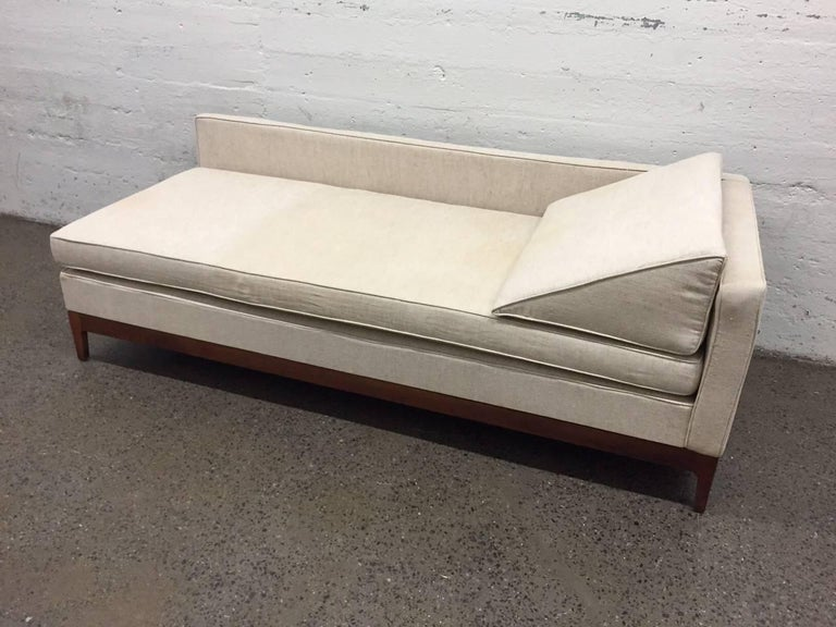 Upholstered daybed with a walnut base. Has loose cushioned seat and headrest.