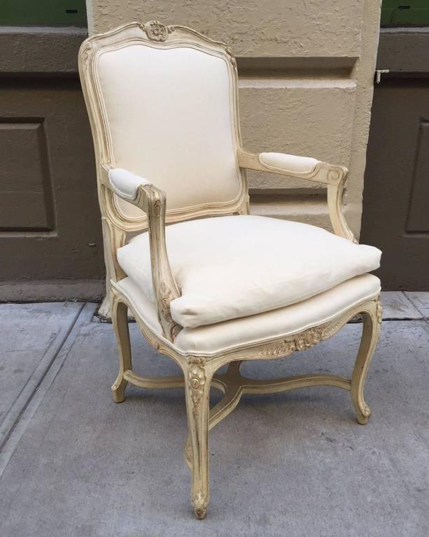 Pair of Louis XIV style armchairs. The chairs have a painted wood, carved frame in an off-white upholstered fabric.