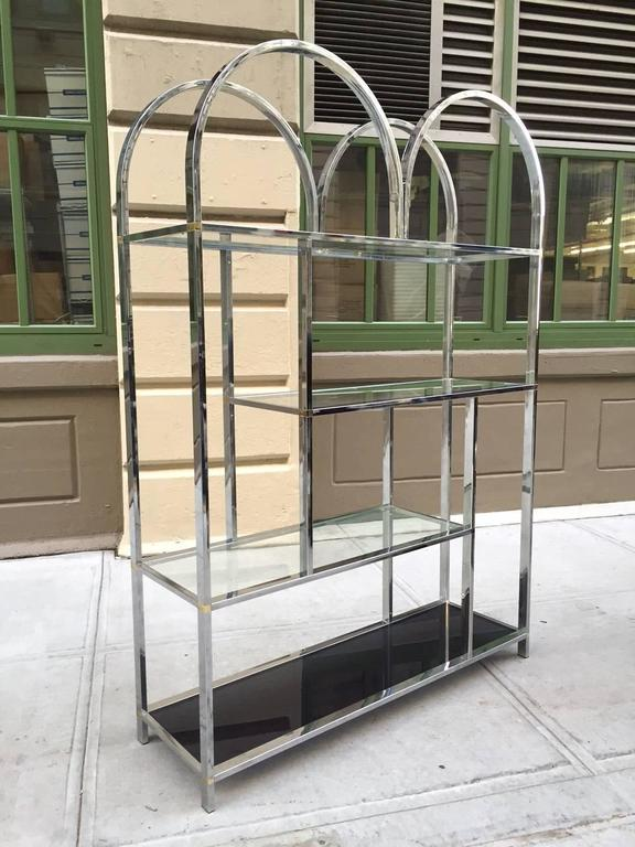Large chrome Etagere style of Milo Baughman. Has curved top, four glass shelves (smoked glass to the bottom), and brass accents.