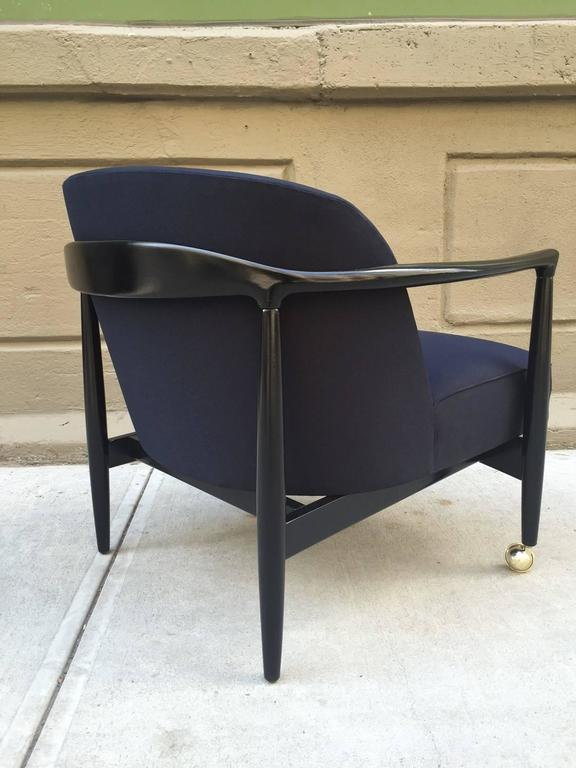Pair of sculptural Ib Kofod-Larsen lounge chairs. Casters to the front legs. Black lacquered sculptural frame. Newly upholstered. The upholstery is a lighter black than the frame.