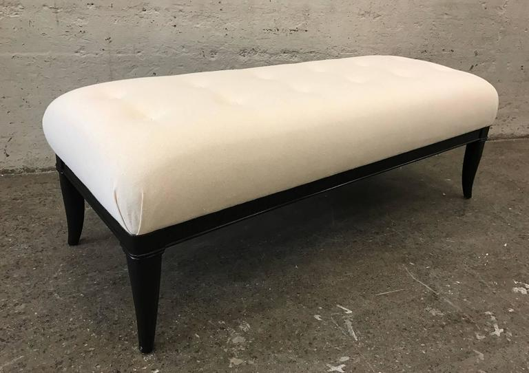 Upholstered tufted bench style of Robsjohn-Gibbings. Black lacquered wood legs with a newly upholstered linen-blend fabric.