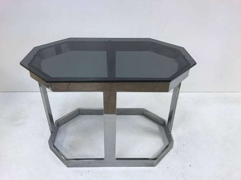 Pair of Milo Baughman chrome and glass tables. Has smoked glass tops, octagonal shape and flat chrome frames.