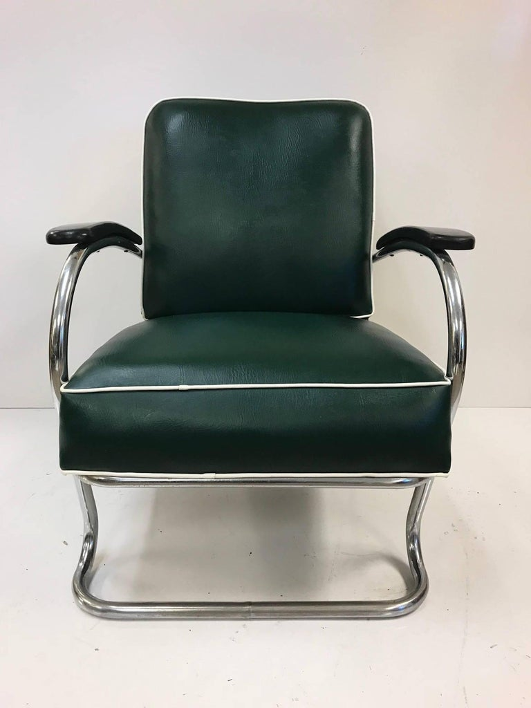 Pair of KEM Weber for Lloyd Tubular chrome lounge chairs. Chairs are vinyl with a steel frame. Chairs have original fabric and are of a hunter green color with white trim.