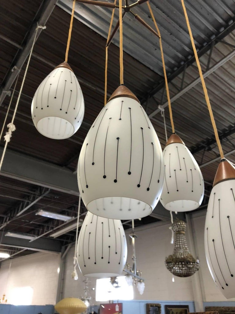 Mid-Century Modern five-pendant light fixture. Has etched glass shades. The tops of the shades are solid walnut. The ceiling cap at the top of the light fixture is brass.