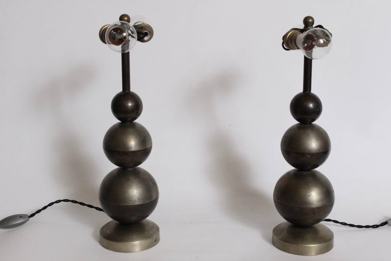 Rare European Art Deco patinated nickel-plated brass table lamps. Featuring triple stacked ball form with top half in nickel plate and bottom half brass. Dome shade exterior in nickel-plated spun brass with Brass interior. Ceramic double brass