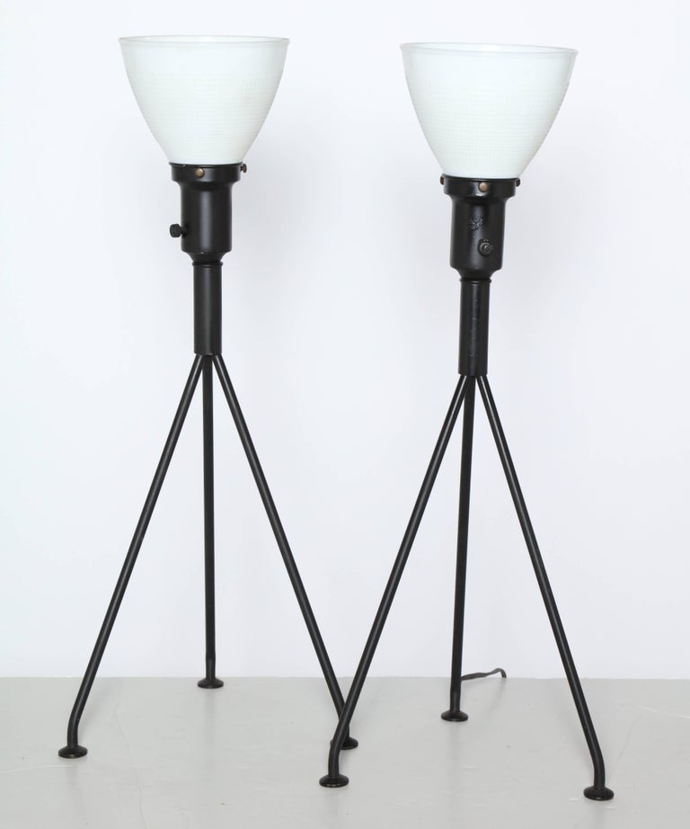 Pair of 1950s Gerald Thurston for Lightolier black and white table lamps. Featuring black enameled steel tripod legs, socket and neck. With white milk glass liner shades and brass feet. For use with or without a Lamp shade. Minimalist. Sculptural.