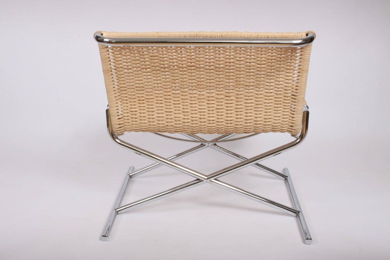 Chromed Steel and Rattan Lounge Chair by Ward Bennett for Brickell. Wide Slipper Chair. Featuring a low chromed X frame, cane covered arms, and curved cane back with rear Chrome detail. Classic. Comfortable. With new caning.