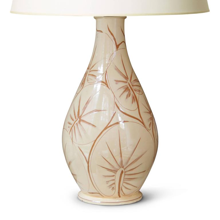 Monumental / tall table lamp with vase form by Kähler Keramik, in hand-turned earthenware, glazed in ivory and incised with a vigorous and masterful sgraffito pattern of tropical leaves of an orbicular or palmate sort; Denmark, mid-20th century,