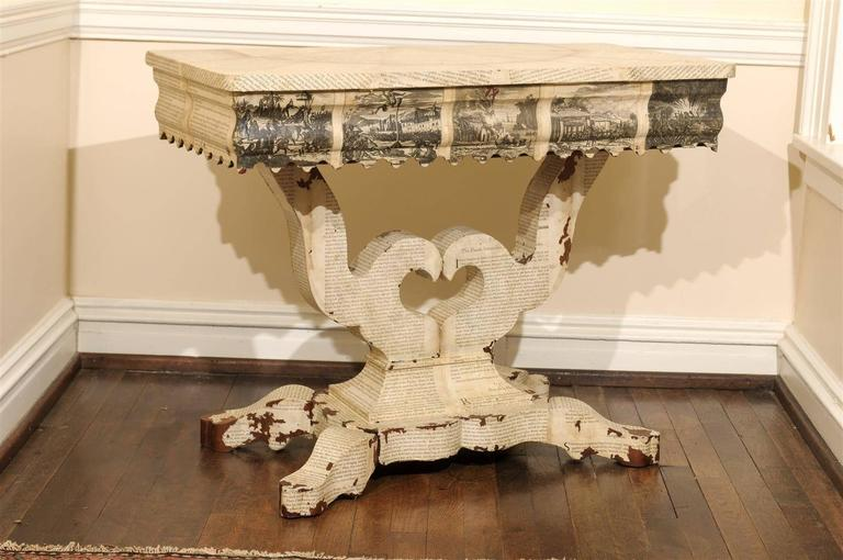 19th century American Empire console table decoupaged in antique texts about America. The pages on top are layed out in a demilune pattern and the frieze is covered in depictions of colonists and native Americans.