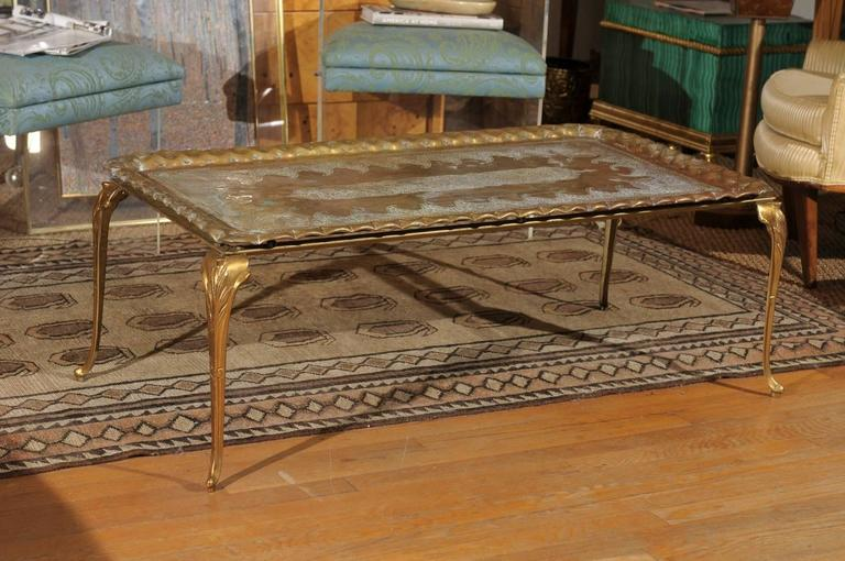 Mid-20th century etched and hammered rectangular oversized brass tray resting on a solid brass stand with cabriole legs.