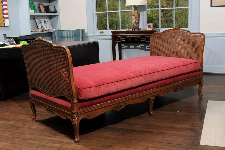 19th Century French Provençal daybed of cane and walnut in the style of Louis XV. The custom red velvet cushion rests on a platform with six carved cabriole legs joined buy floral carved and scalloped aprons and bordered by decorative nailheads. The